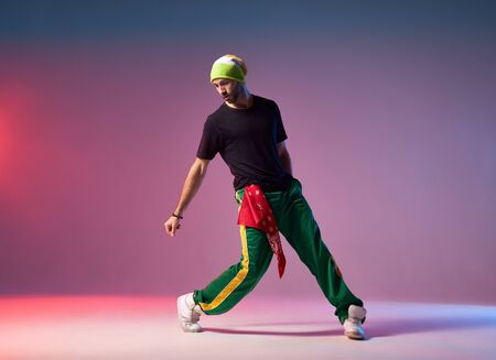 Professional breakdancer in motion on studio stage, performing energetic dance, looking down, exercising with strength to win on competition