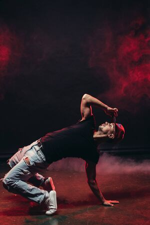 athletic male dancing street dance isolated over smoky background, stylish modern type of dance