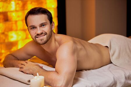 Portrait of young caucasian man lying on massage table at spa center with naked skin, massage on back and shoulders. Фото со стока - 134663944