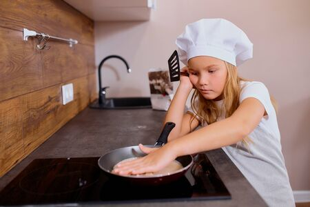 tired and ored little girl in kitchen while baking, caucasian child wearing apron and cap for cooking put circle dough on pan. Reklamní fotografie