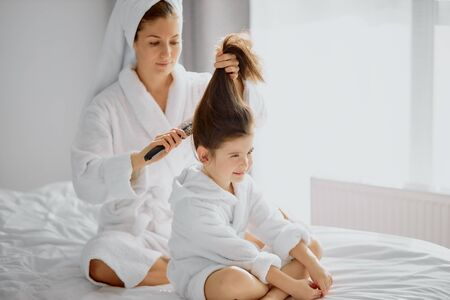 beautiful caucasian woman sit combing hair to lovely daughter, tidy up after shower in bright white bedroom. in bathrobes Reklamní fotografie