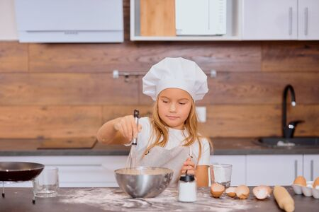 portrait of beautiful nice kid girl mixing dough for baking cakes in kitchen, wearing apron Reklamní fotografie