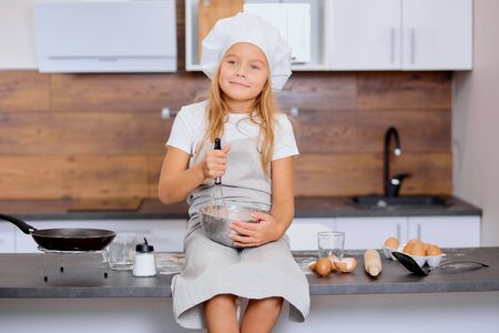 portrait of beautiful dreamy nice kid girl mixing dough for baking cakes in kitchen