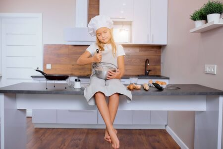 portrait of beautiful nice kid girl mixing dough for baking cakes in kitchen
