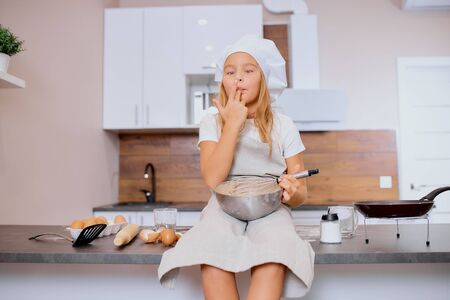 portrait of little caucasian girl trying, eating dough while independently baking. Reklamní fotografie