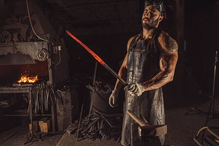 handsome muscular male blacksmith holding handmade metal for manufacturing, wearing leather apron or uniform.