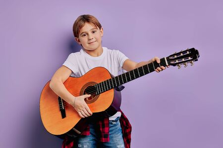 portrait of caucasian little boy 7-8 years old stand holding acoustic guitar 스톡 콘텐츠