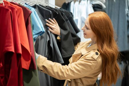 attractive woman with red hair happily looking for, searching beautiful clothes for herself, choosing best wear in shopping store 版權商用圖片
