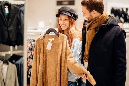 young caucasian couple happily shopping in clothes store together, spend free time in shop. shopaholic concept 版權商用圖片