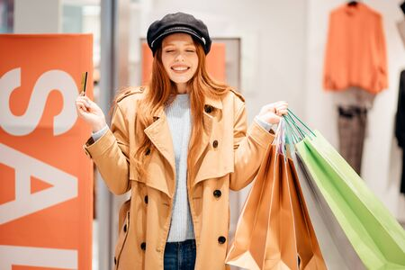 shopping concept. young caucasian shopaholic with red hair raised hands up, holdig paper bags full of new trendy clothes dresses
