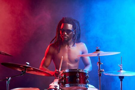 awesome black man with naked skin playing on drums, isolated over neon smoky background