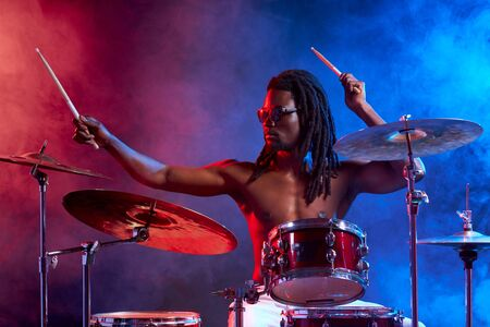 portrait of talented african man playing on drums, with naked skin wearing eyeglasses isolated over smoky neon background