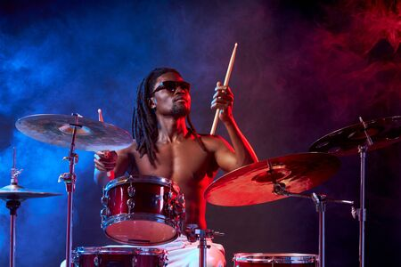 vigorous male with naked skin playing on drums isolated over neon smoky background, wearing eyeglasses 免版税图像