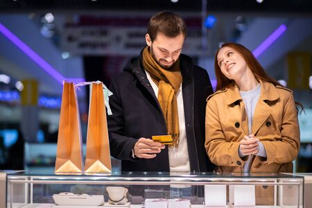 lovely couple choosing expensive golden or silver jewelry at shop, smiling happy female with red hair and bearded man wearing coat 版權商用圖片