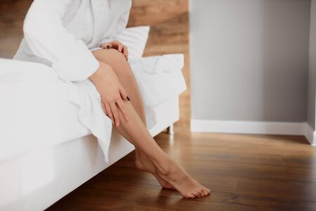 Tender female hands examining long straight slender legs with smooth silky skin after hair removal cosmetology procedure.