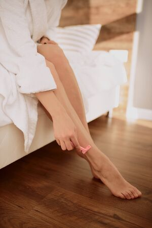 Female gentle hand holding pink razor, making depilation, young woman cares about legs.