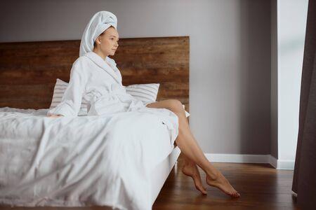 Tender pleasant female wearing white soft bathrobe and having towel on head, leaning on bed. 版權商用圖片