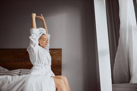 Charming young girl raising hands up, enjoying morning sun light, wearing comfortable bathrobe after shower.