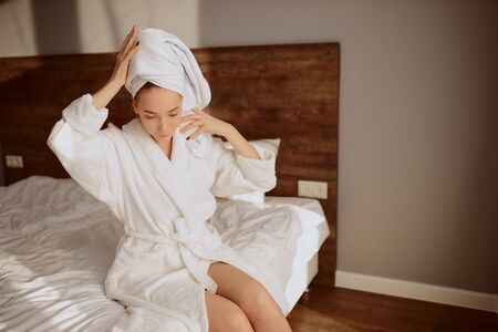 Cheerful female model enjoying time alone in bedroom after shower