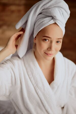 Beautiful young woman after bath with towel wrapped on head
