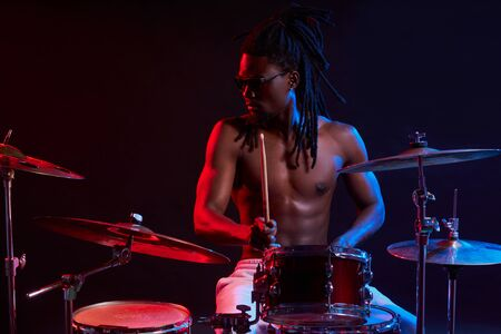 Portrait of active african man playing on drums set in neon lights, wearing eyeglasses, performing music.