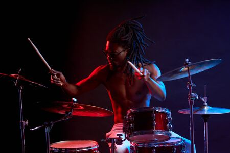 portrait of young african male playing on drums isolated over neon light background