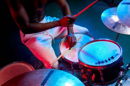 close-up of mans hands playing on drums, african man with skin in neon lights