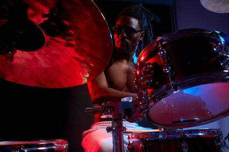 good-looking artistic african black male drummer enjoying playing drums over dark background