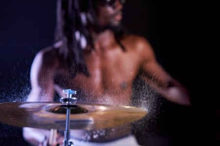 black male with dreadlocks rehearsing on drums before his rock concert, water drops on drums. close-up 版權商用圖片