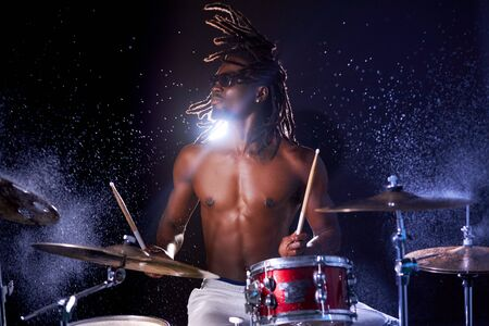 wet drum set covered with water drops, african young man beating on drum set with sticks. skillful black drummer with naked skin and dreadlocks