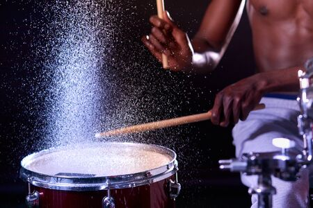 cropped african young naked male holding drum sticks in water, performing music