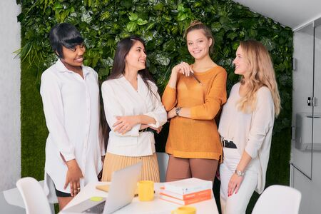 Smiling enthusiastic women coworking together in modern office, look at each other and at camera