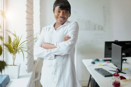 portrait of pretty african american business lady wearing white shirt in office stand near window posing.