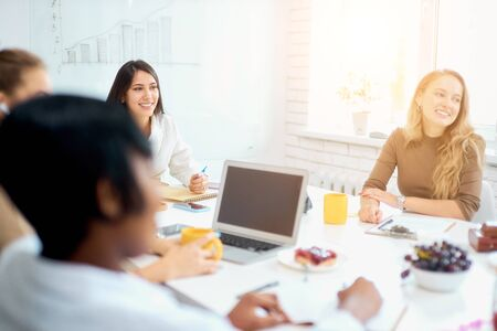 Young creative business ladies coworking in white modern office, wearing casual clothes. use laptop, modern technologies