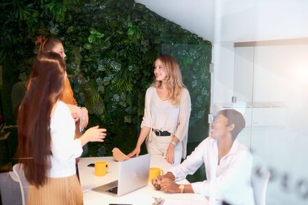 Caucasian business women develop new project with african representative, young female teamwork in modern office