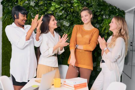 young diverse women clapping hands to their caucasian colleague at work place, celebrating 스톡 콘텐츠