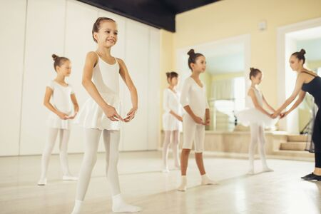 Attraente e bella donna caucasica che indossa gonna tutu nera mostra pose giuste nel balletto per bambini piccoli, eseguendo la danza classica in studio, isolata nella scuola di danza