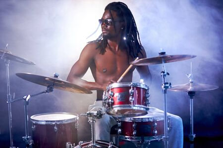 black young guy with dreadlocks wearing eyeglasses sit beating on drums with sticks, with naked skin isolated over smoky background
