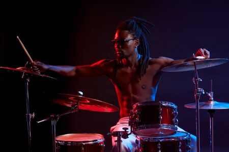 Portrait of active african man playing on drums set in neon lights, wearing eyeglasses, performing music. expressive emotions and movement