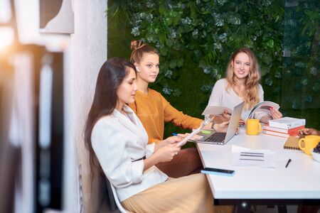 successful coworking of caucasian women, togetherness in work. confident enthusiastic female gathered to discuss, speak in executive modern office