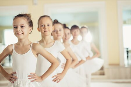 little caucasian girls in white tutu skirts and pointe shoes dream of becoming great ballerinas, training, practicing classic ballet dance in studio, group of little caucasian graceful girls