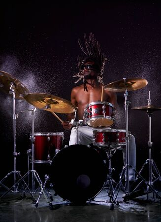 portrait of african man performing music with use of drum set, handsome black naked man Stock Photo