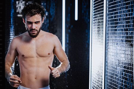 young caucasian bearded man with athletinc fit body take shower indoors, strong muscular male in bathroom