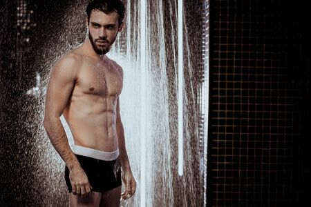 handsome man with strong muscles, perfect body stand under running water taking shower Stock Photo