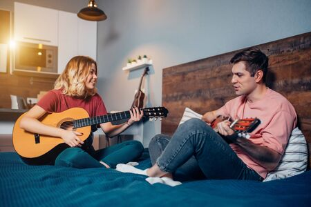 lovely couple, young people playing guitar together at home sitting on bed. caucasian girl and boy wearing casual home clothes Archivio Fotografico
