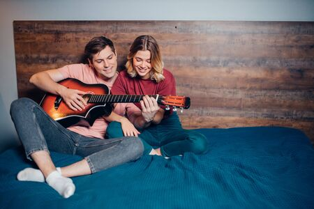 two romantic people in love sit together on bed, playing the guitar. caucasian people sit together at home Archivio Fotografico