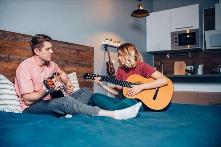 due romantici innamorati si siedono insieme sul letto, suonando la chitarra. i caucasici si siedono insieme a casa
