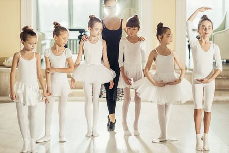 little girls ballerinas stand in tiptoes isolated in studio, dressed in white tutu skirts and pointe shoes, group of diligent caucasian girls practicing before performance Stock Photo