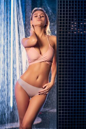 beautiful caucasian young shirtless woman taking shower wearing underwear, enjoy and relax under shower, modern and fresh