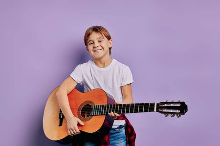 portrait of caucasian handsome boy 7-8 years old stand holding acoustic guitar, student of music school, posing with guitar. children interested in music and instruments. isolated purple background